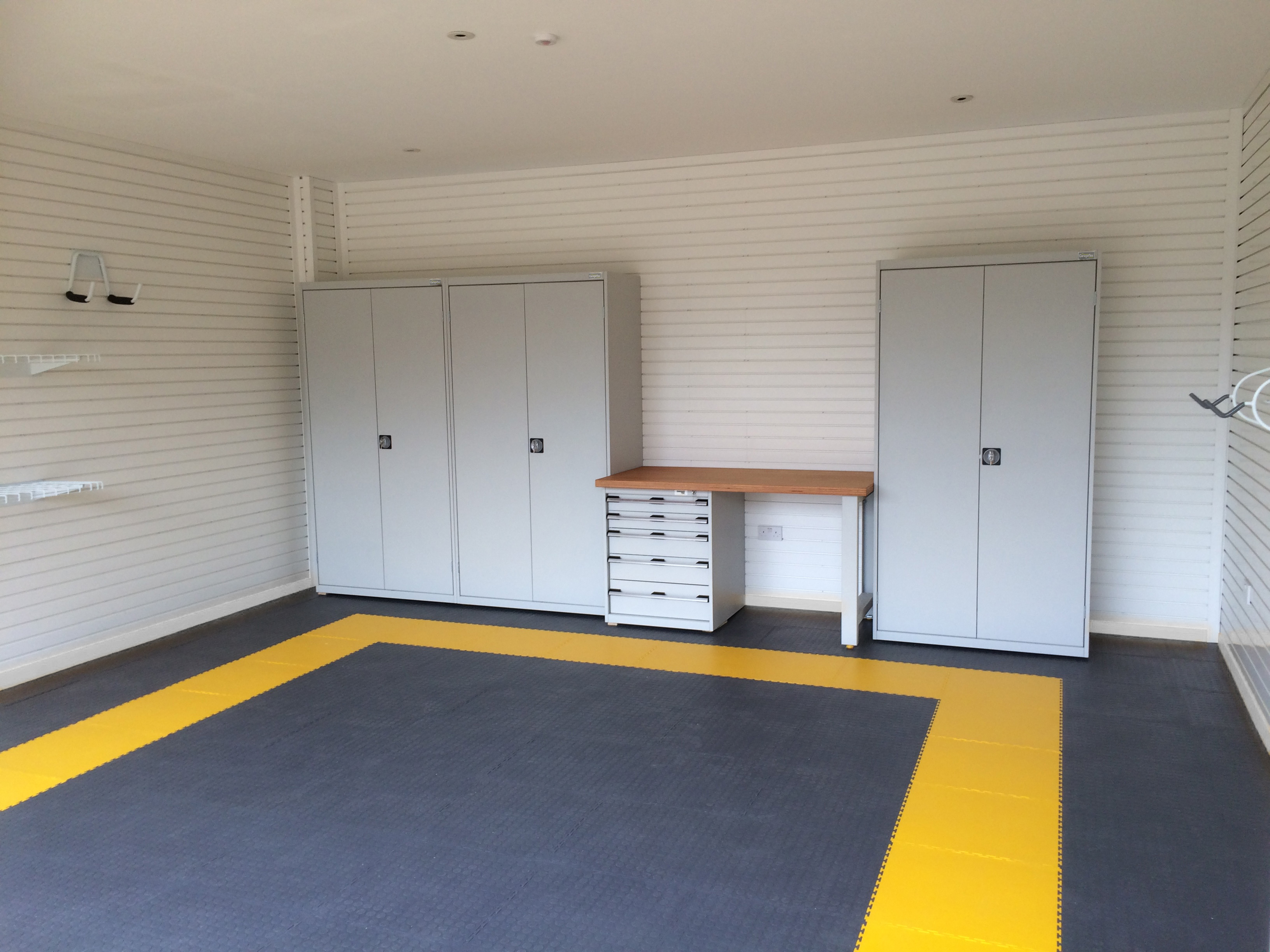 Dark Grey floor tiles with a yellow border look great in this garage
